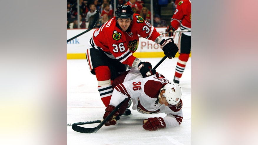 Chicago Blackhawks' Dave Bolland, left, takes Phoenix Coyotes' Rob Klinkhammer, right, to the ice during the first period of an NHL hockey game on Saturday, Apr. 20, 2013, in Chicago. (AP Photo/John Smierciak)