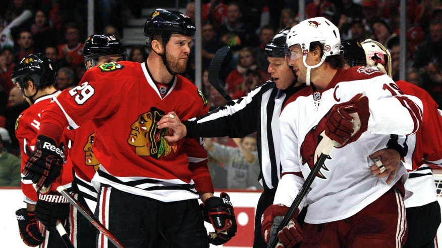 An official separates Chicago Blackhawks' Bryan Bickell, left, and Phoenix Coyotes' Shane Doan during the first period of an NHL hockey game Saturday, April 20, 2013, in Chicago. (AP Photo/John Smierciak)