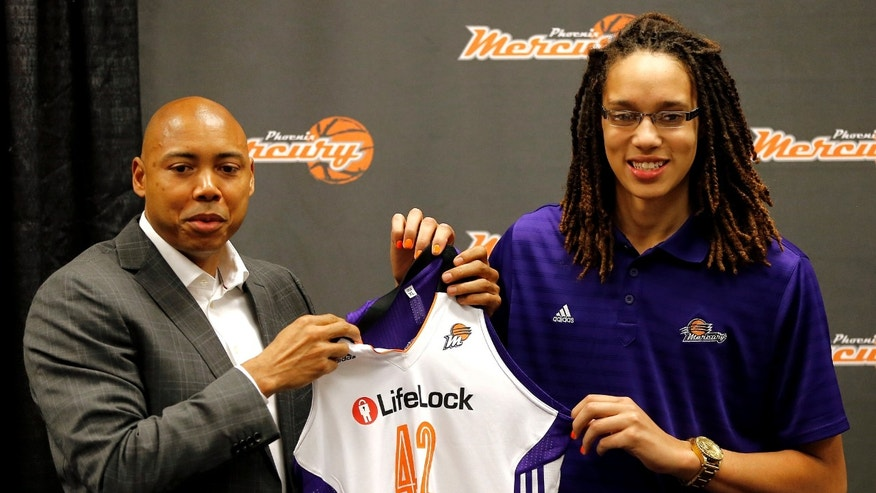 Phoenix Mercury's Brittney Griner, the No. 1 overall pick the WNBA draft, holds a team jersey with head coach Corey Gaines during a news conference Saturday, April 20, 2013,  in Phoenix. (AP Photo/Matt York)