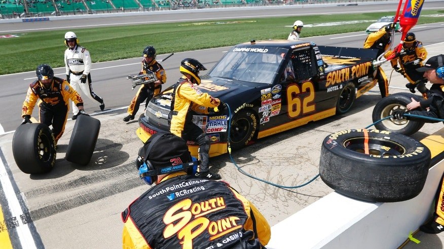 The pit crew works on the truck of Brendan Gaughan during the NASCAR trucks auto race race at Kansas Speedway in Kansas City, Kan., Saturday, April 20, 2013. (AP Photo/Orlin Wagner)