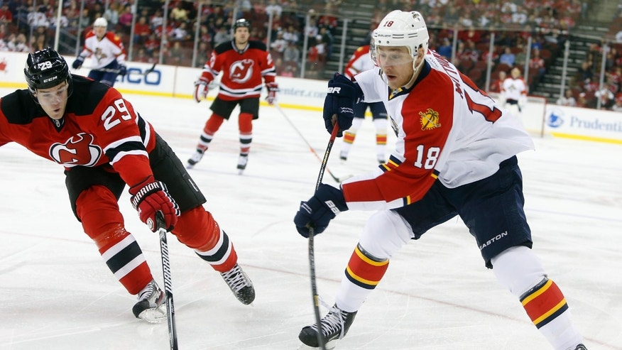 Florida Panthers center Shawn Matthias (18) passes the puck away from New Jersey Devils defenseman Mark Fayne (29) during the first period of an NHL hockey game, Saturday, April 20, 2013, in Newark, N.J. (AP Photo/Jason DeCrow)