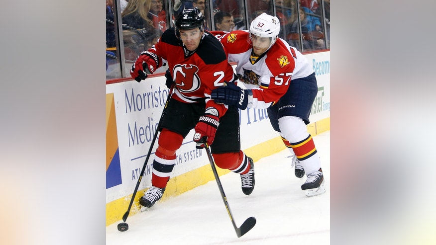 New Jersey Devils defenseman Marek Zidlicky (2) battles for possession with Florida Panthers center Marcel Goc (57) during the first period of an NHL hockey game, Saturday, April 20, 2013, in Newark, N.J. (AP Photo/Jason DeCrow)