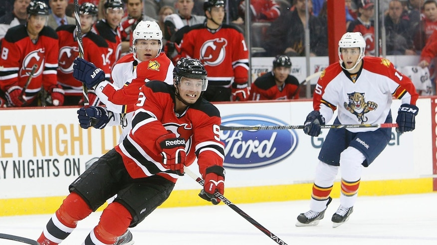 New Jersey Devils center Jacob Josefson (9) passes the puck away from Florida Panthers defenseman Dmitry Kulikov, left, during the first period of an NHL hockey game, Saturday, April 20, 2013, in Newark, N.J. (AP Photo/Jason DeCrow)