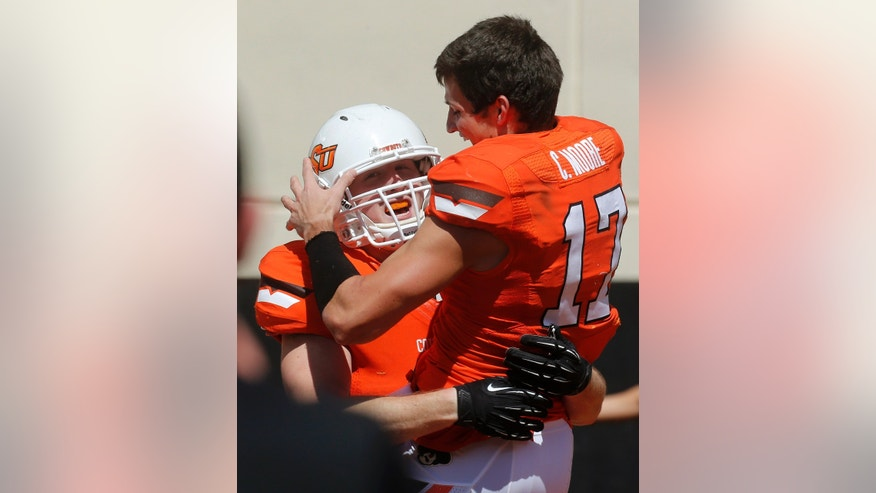 Oklahoma State linebacker Caleb Lavey (45) celebrates with Charlie Moore (17) after running back an interception for a touchdown during the NCAA college football team's spring game in Stillwater, Okla., Saturday, April 20, 2013. (AP Photo/Sue Ogrocki)