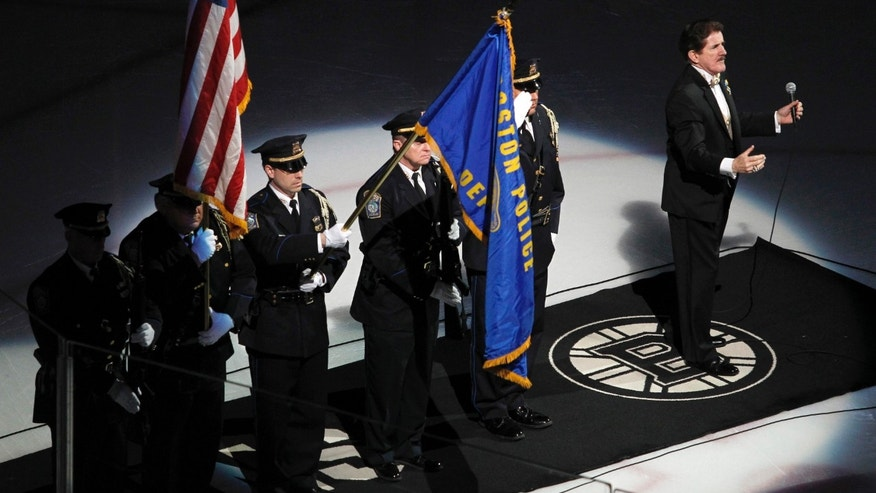 Rene Rancourt, right, conducts the crowd in the singing of the national anthem as the Boston Police honor guard presents the colors before the start of an NHL hockey game between the Pittsburgh Penguins and Boston Bruins, Saturday, April 20, 2013, in Boston.  (AP Photo/Mary Schwalm)