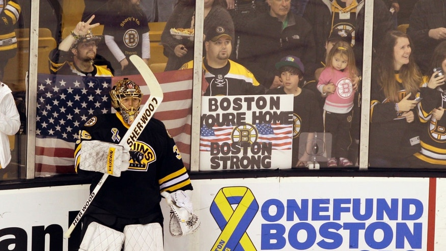 Boston Bruins goalie Anton Khudobin (35) pauses during warm ups before an NHL hockey game against the Pittsburgh Penguins, Saturday, April 20, 2013, in Boston. A fan holds up a sign of support for the city in the background, (AP Photo/Mary Schwalm)
