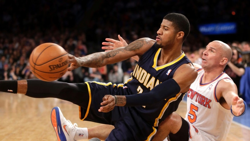 Indiana Pacers' Paul George, left, passes the ball after tumbling to the court with New York Knicks' Jason Kidd during the first half of the NBA basketball game, Sunday, April 14, 2013, in New York. (AP Photo/Seth Wenig)