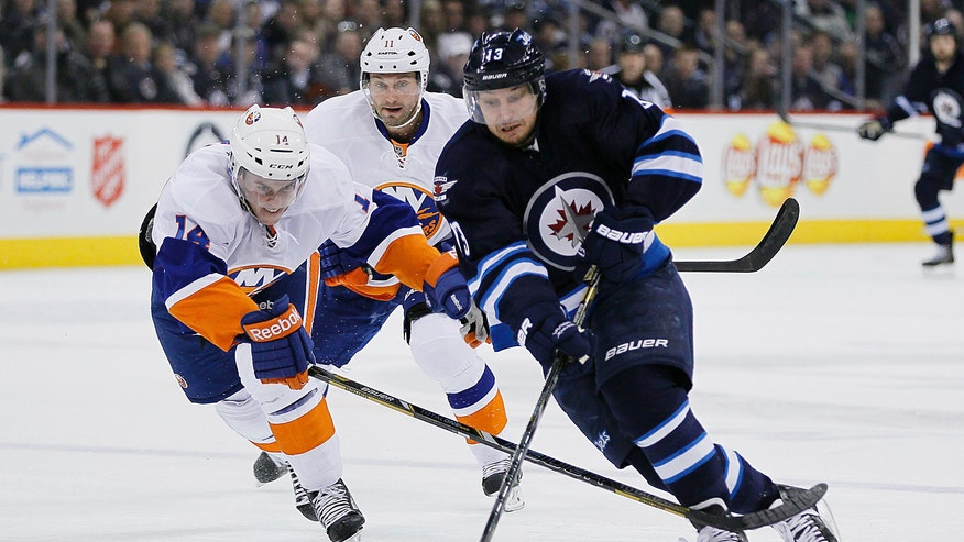 Winnipeg Jets' Kyle Wellwood (13) steals the puck from New York Islanders' Thomas Hickey (14) to score on a breakaway against goaltender Evgeni Nabokov (20) during the second period of an NHL game in Winnipeg, Manitoba, Saturday, April 20, 2013. (AP Photo/The Canadian Press, John Woods)