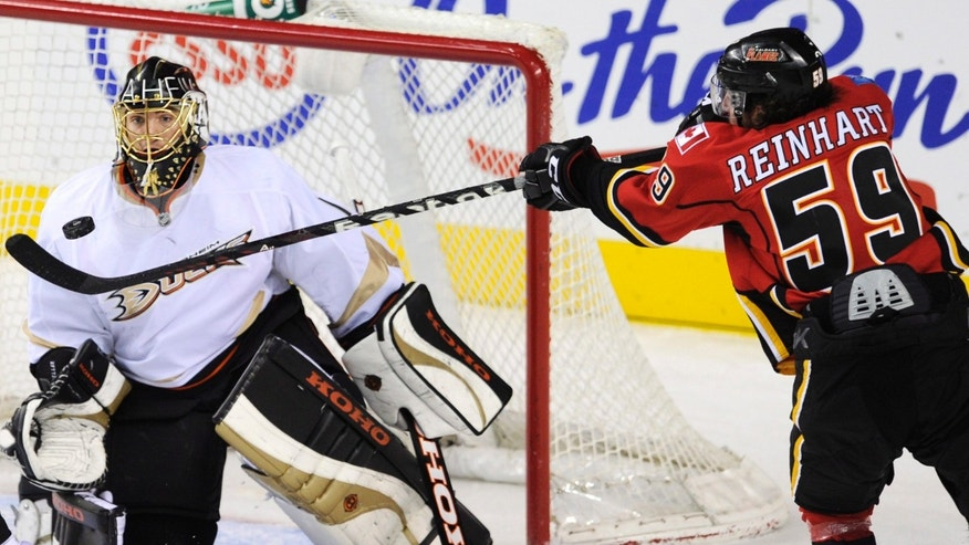 Calgary Flames' Max Reinhart, right, tries to bat the puck out of the air toward Anaheim Ducks goalie Jonas Hiller, from Switzerland, during second-period NHL hockey action in Calgary, Alberta, Friday, April 19, 2013. (AP Photo/The Canadian Press, Larry MacDougal)