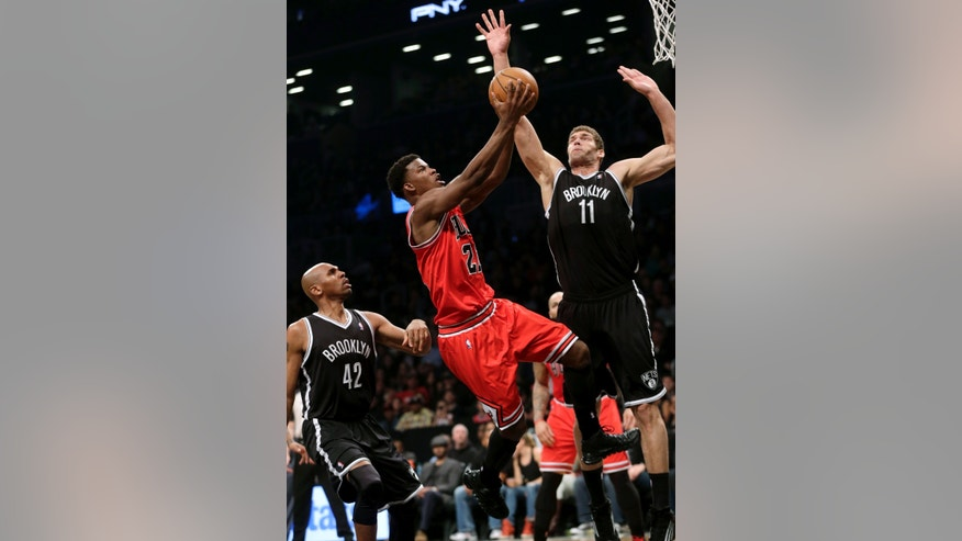 Chicago Bulls' Jimmy Butler, center, drives to the basket through Brooklyn Nets' Jerry Stackhouse, left, and Brook Lopez during the first quarter of Game 1 of a first-round series of the NBA basketball playoffs, Saturday, April 20, 2013, in New York. (AP Photo/Seth Wenig)