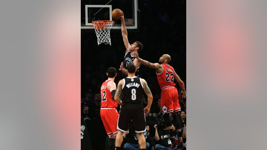 Brooklyn Nets' Brook Lopez, top, dunks against the Chicago Bulls during the first quarter of Game 1 of a first-round series of the NBA basketball playoffs, Saturday, April 20, 2013, in New York. (AP Photo/Seth Wenig)