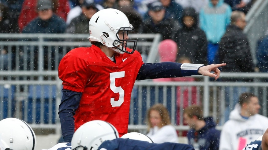 Snow falls around Penn State quarterback Tyler Ferguson as he calls signals in the first half of a spring NCAA college football game on Saturday, April 20, 2013 in State College, Pa. (AP Photo/Keith Srakocic)
