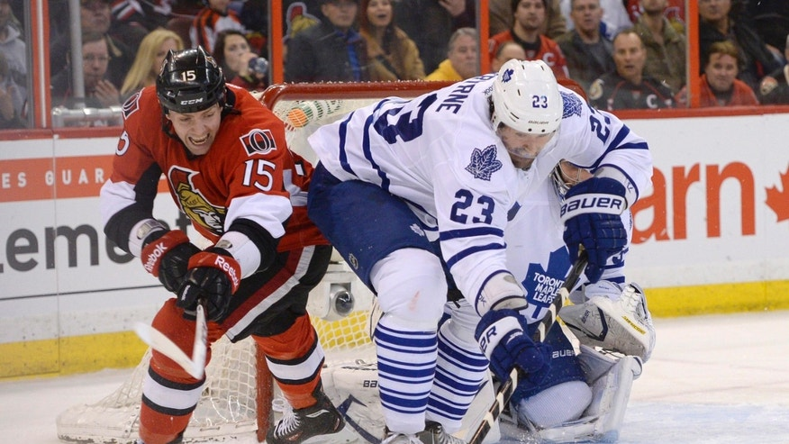 Toronto Maple Leafs' Ryan O'Byrne (23) keeps Ottawa Senators' Zack Smith (15) away from the puck during the first period of an NHL hockey game in Ottawa, Ontario, Saturday, April 20, 2013. (AP Photo/The Canadian Press, Justin Tang)