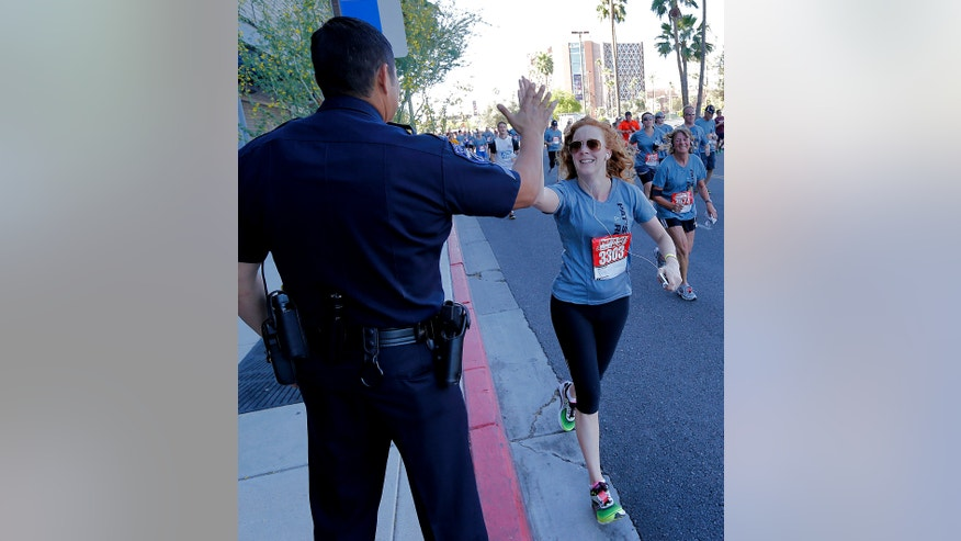 A runner high-fives a Tempe Police officer along the route during the 9th annual Pat's Run, Saturday, April 20, 2013, in Tempe, Ariz.  Pat's Run is a celebration of the life of Pat Tillman, the NFL star who walked away from millions of dollars to become and Army Ranger after the Sept. 11 terrorist attacks. The 4.2-mile run through the streets of Tempe takes on added significance following the bombings at the Boston Marathon. (AP Photo/Matt York)