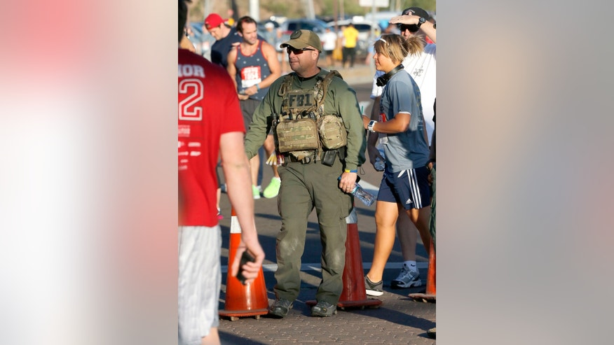 A law enforcement officer stands among the crowd during the 9th annual Pat's Run, Saturday, April 20, 2013, in Tempe, Ariz.  Pat's Run is a celebration of the life of Pat Tillman, the NFL star who walked away from millions of dollars to become and Army Ranger after the Sept. 11 terrorist attacks. The 4.2-mile run through the streets of Tempe takes on added significance following the bombings at the Boston Marathon. (AP Photo/Matt York)