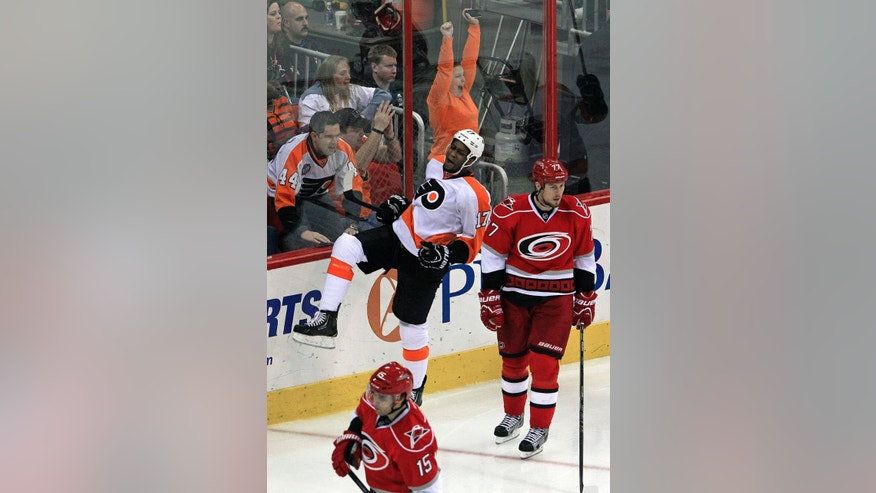 Philadelphia Flyers' Wayne Simmonds (17) celebrates his third goal of the night for a hat trick with Carolina Hurricanes' Joe Corvo (77) and Tuomo Ruutu (15), of Finland, nearby during the third period of an NHL hockey game on Saturday, April 20, 2013, in Raleigh, N.C. The Flyers won 5-3. (AP Photo/Karl B DeBlaker)