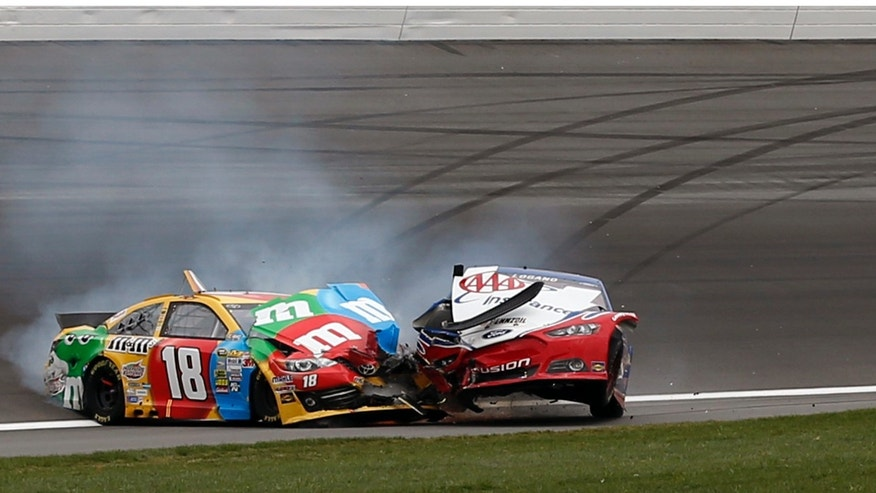 Kyle Busch (18) and Joey Logano (22) wreck during a NASCAR Sprint Cup series auto race at Kansas Speedway in Kansas City, Kan., Sunday, April 21, 2013. (AP Photo/Orlin Wagner)