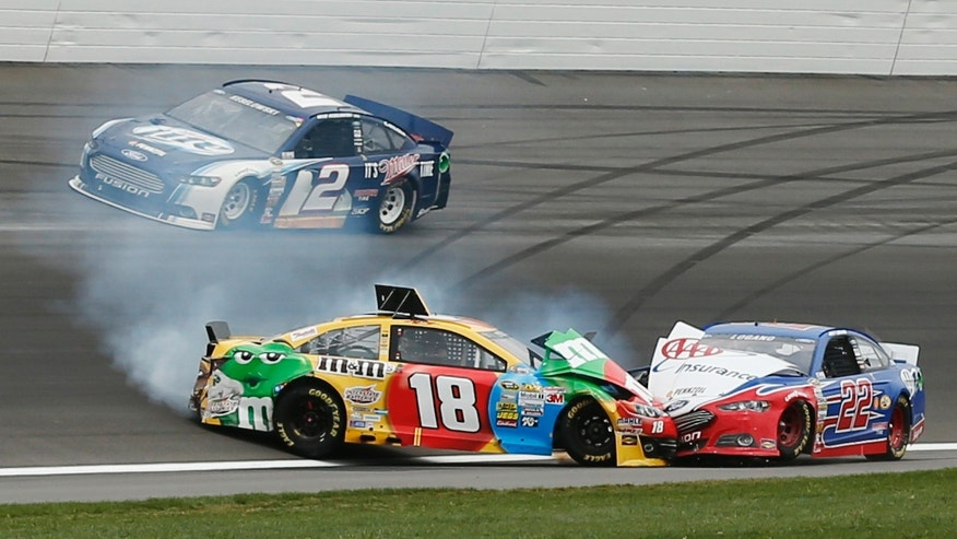 Brad Keselowski (2) avoids Kyle Busch (18) and Joey Logano (22) as they wreck during a NASCAR Sprint Cup series race at Kansas Speedway in Kansas City, Kan., Sunday, April 21, 2013. (AP Photo/Orlin Wagner)