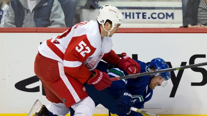 Detroit Red Wings' Jonathan Ericsson, left, of Sweden, checks Vancouver Canucks' Daniel Sedin, of Sweden, during the first period of an NHL hockey game in Vancouver, British Columbia, on Saturday, April 20, 2013. (AP Photo/The Canadian Press, Darryl Dyck)
