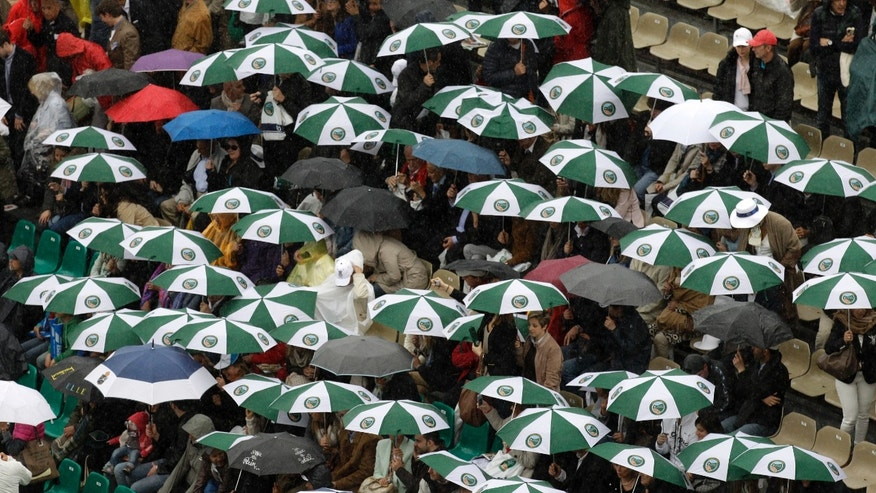 Spectators wait under umbrellas on the central court of the Monte Carlo Tennis Masters tournament in Monaco before the final match between Novak Djokovic of Serbia and Rafael Nadal of Spain, Sunday, April 21, 2013. (AP Photo/Lionel Cironneau)