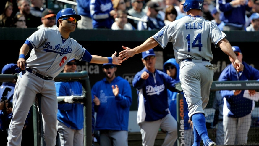Los Angeles Dodgers' A.J. Ellis (14) is congratulated by Jerry Hairston, left, after scoring against the Baltimore Orioles in the fifth inning of a baseball game, Sunday, April 21, 2013, in Baltimore. (AP Photo/Gail Burton)