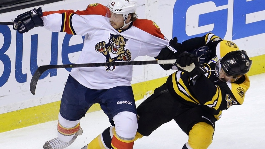 Florida Panthers right wing Jack Skille (12), left, grapples with Boston Bruins defenseman Johnny Boychuk (55), right, in the first period of an NHL hockey game at the TD Garden, in Boston, Sunday, April 21, 2013. (AP Photo/Steven Senne)