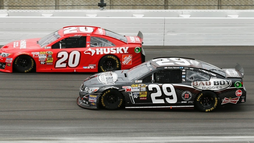 Driver Matt Kenseth (20) holds off Kevin Harvick (29) during a NASCAR Sprint Cup series race at Kansas Speedway in Kansas City, Kan., Sunday, April 21, 2013. (AP Photo/Orlin Wagner)