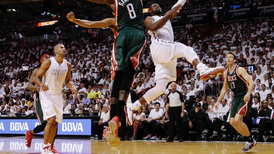 Miami Heat's Dwyane Wade (3) goes to the basket as Milwaukee Bucks' Larry Sanders (8) defends during the first half of Game 1 of their first-round NBA basketball playoff series in Miami, Sunday April 21, 2013. (AP Photo/Alan Diaz)