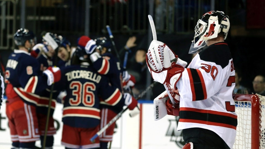New Jersey Devils goalie Martin Brodeur, right, looks on as the New York Rangers celebrate a goal during the second period of an NHL hockey game on Sunday, April 21, 2013, in New York. (AP Photo/Seth Wenig)