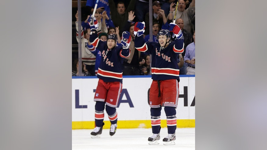 New York Rangers' Derek Stepan, right, celebrates his goal with Ryane Clowe during the first period of an NHL hockey game against the New Jersey Devils, Sunday, April 21, 2013, in New York. (AP Photo/Seth Wenig)