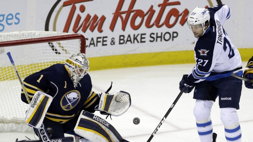 Buffalo Sabres goalie Jhonas Enroth of Sweden makes a save on a shot by Winnipeg Jets' Eric Tangradi (27) during the first period of an NHL hockey game in Buffalo, N.Y., Monday, April 22, 2013. (AP Photo/David Duprey)