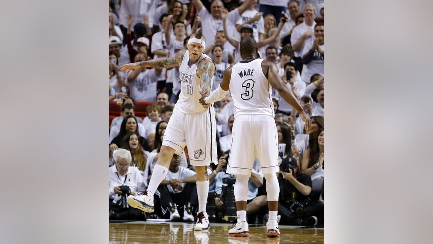Miami Heat's Dwyane Wade (3) congratulates Chris Andersen (11) after Andersen scored against the Milwaukee Bucks during the second half of Game 1 of their first-round NBA basketball playoff series in Miami, Sunday April 21, 2013. The Heat won 110-87. (AP Photo/Alan Diaz)