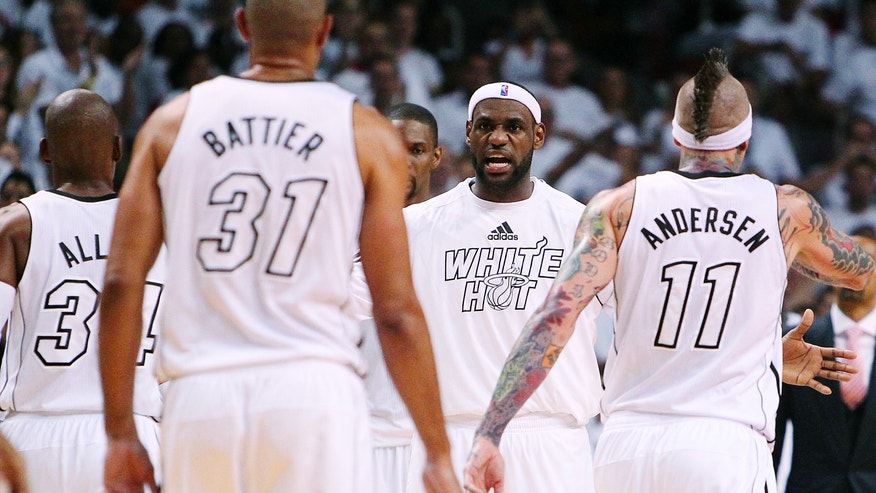 Miami Heat forward LeBron James, center, congratulates Ray Allen (34), Shane Battier (31) and Chris Andersen (11) during the fourth quarter of Game 1 of their first-round NBA basketball playoff series against the Milwaukee Bucks in Miami, Sunday, April 21, 2013. The Heat won 110-87. (AP Photo/El Nuevo Herald, David Santiago)  MAGS OUT
