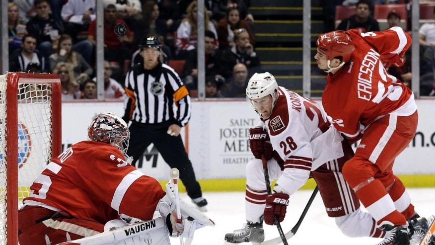 Detroit Red Wings goalie Jimmy Howard, left, stops a shot by Phoenix Coyotes center Lauri Korpikoski (28), of Finland, as Detroit Red Wings defenseman Jonathan Ericsson, of Sweden, defends in the first period of an NHL hockey game in Detroit, Monday April 22, 2013. (AP Photo/Paul Sancya)