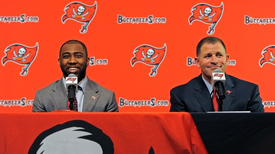 NFL cornerback Darrelle Revis, left, and head coach Greg Schiano address the media while announcing that the Buccaneers have acquired Revis from the New York Jets during an NFL football press conference Monday, April, 22, 2013, in Tampa, Fla. The Buccaneers and Revis have agreed on a six-year contract. (AP Photo/Brian Blanco)
