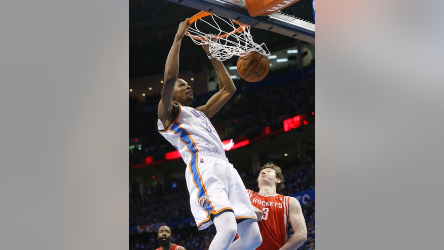 Oklahoma City Thunder forward Kevin Durant (35) dunks in front of Houston Rockets center Omer Asik (3) in the third quarter of Game 1 of their first-round NBA basketball playoff series in Oklahoma City, Sunday, April 21, 2013. Oklahoma City won 120-91. (AP Photo/Sue Ogrocki)