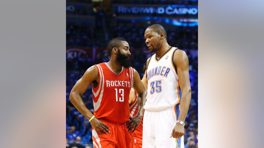 Houston Rockets guard James Harden (13) talks with Oklahoma City Thunder forward Kevin Durant (35) during a time out in the second quarter of Game 1 of their first-round NBA basketball playoff series in Oklahoma City, Sunday, April 21, 2013. Oklahoma City won 120-91. (AP Photo/Sue Ogrocki)