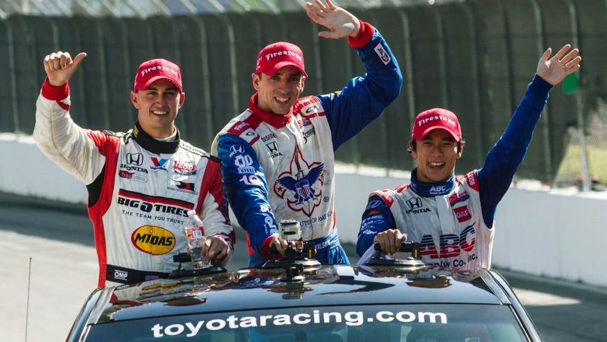 From left, Graham Rahal, Justin Wilson, of England, and Takuma Sato, of Japan, wave to fans as they take their victory lap after the IndyCar Series Grand Prix of Long Beach auto race, Sunday, April 21, 2013, in Long Beach, Calif.  Sato took first, Rahal second and Wilson third. (AP Photo/Ringo H.W. Chiu)