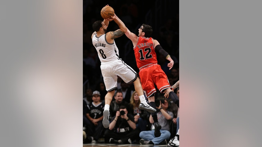 Chicago Bulls guard Kirk Hinrich (12) defends as Brooklyn Nets guard Deron Williams (8) shoots in the second half of Game 2 of their first-round NBA basketball playoff series, Monday, April 22, 2013, in New York. The Bulls won 90-82. (AP Photo/Kathy Willens)