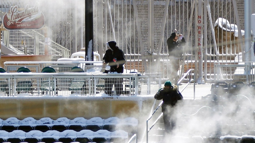 Mainelle Moore, right, hoses down snow-covered seats in the right field at Target Field with hot water prior to the start of the first game of a day/night baseball double header against the Miami Marlins Tuesday, April 23, 2013 in Minneapolis, Minn. Monday's game was postponed due to snow. (AP Photo/Jim Mone)