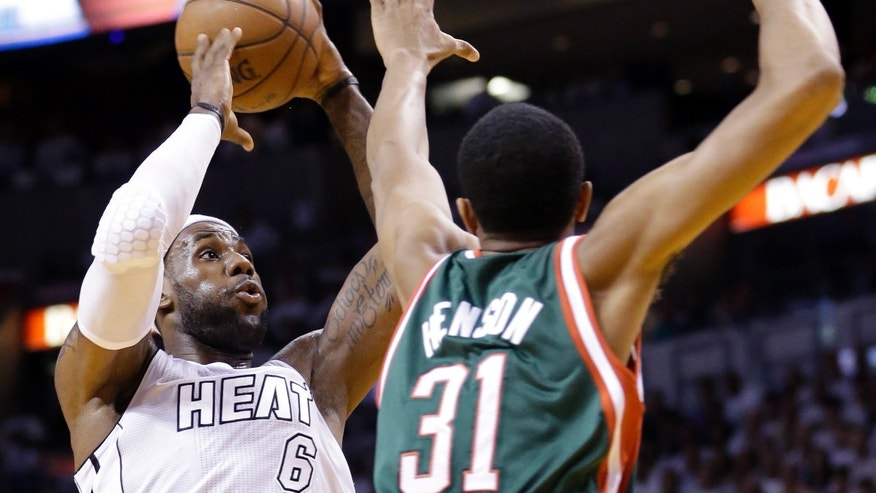 Miami Heat forward LeBron James (6) shoots against Milwaukee Bucks forward John Henson (31) during the first half of Game 2 in their first-round NBA basketball playoff series, Tuesday, April 23, 2013 in Miami. (AP Photo/Wilfredo Lee)
