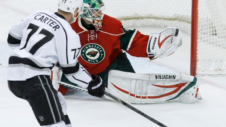 Minnesota Wild goalie Niklas Backstrom (32), of Finland, stops a shot by Los Angeles Kings center Jeff Carter (77) during the first period of an NHL hockey game in St. Paul, Minn., Tuesday, April 23, 2013. (AP Photo/Ann Heisenfelt)