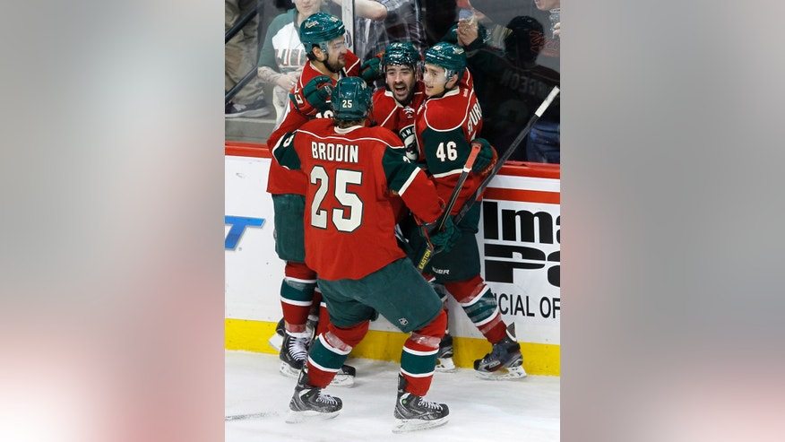 Minnesota Wild right wing Cal Clutterbuck (22), center, celebrates with teammates Devin Setoguchi, left,  Jared Spurgeon (46), and Jonas Brodin (25) after Clutterbuck scored on Los Angeles Kings goalie Jonathan Bernier during the first period of an NHL hockey game in St. Paul, Minn., Tuesday, April 23, 2013. (AP Photo/Ann Heisenfelt)