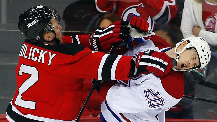 New Jersey Devils' Marek Zidlicky (2) of the Czech Republic checks Montreal Canadiens' Colby Armstrong (20) during the third period of an NHL hockey game in Newark, N.J., Tuesday, April 23, 2013. The Devils defeated the Canadiens 3-2. (AP Photo/Rich Schultz)