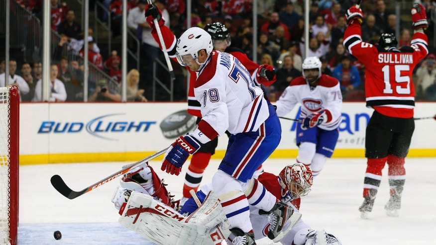 New Jersey Devils' Steve Sullivan (15) celebrates his goal as Montreal Canadiens' Andrei Markov (79) of Russia knocks away the puck in front of goalie Carey Price (31) during the second period of an NHL hockey game in Newark, N.J., Tuesday, April 23, 2013. (AP Photo/Rich Schultz)