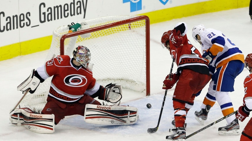 New York Islanders' Kyle Okposo (21) scores on Carolina Hurricanes goalie Dan Ellis as Hurricanes' Justin Faulk defends during the third period of an NHL hockey game in Raleigh, N.C., Tuesday, April 23, 2013. Carolina won 4-3 in a shootout. (AP Photo/Gerry Broome)