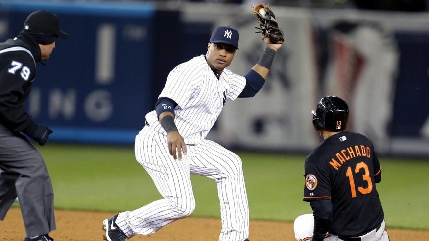 New York Yankees second baseman Robinson Cano, center, waits for the call from second base umpire Manny Gonzalez, left, after tagging Baltimore Orioles' Manny Machado for the third out of a triple play during the eight inning of a baseball game at Yankee Stadium in New York, Friday, April 12, 2013. (AP Photo/Julio Cortez)