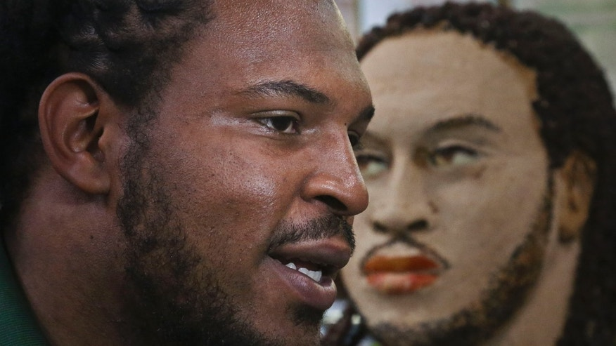 "Jarvis Jones, the top 2013 NFL draft prospect from Georgia, is interviewed after the unveiling of a ""Smokehouse BBQ Chicken"" statue, right, in his likeness to announce his official Subway's Famous Fan title on Tuesday, April 23, 2013 in New York.   Jarvis joins a roster of fellow ""Famous Fans"" that include Robert Griffin III, Justin Tuck, Michael Strahan, Ndamukong Suh, Blake Griffin and Michael Phelps.  More than 10 pounds of chicken were used to create the work of art, made by artist James Victor of Conshohocken, Pa.  (AP Photo/Bebeto Matthews)"