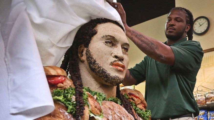 "Jarvis Jones, the top 2013 NFL draft prospect from Georgia, unveils a  ""Smokehouse BBQ Chicken"" statue of himself to announce his official Subway's Famous Fan title on Tuesday, April 23, 2013 in New York.  Jarvis joins a roster of fellow ""Famous Fans"" that include Robert Griffin III, Justin Tuck, Michael Strahan, Ndamukong Suh, Blake Griffin and Michael Phelps.  More than 10 pounds of chicken were used to create the work of art, made by artist James Victor of Conshohocken, Pennsylvania.  (AP Photo/Bebeto Matthews)"