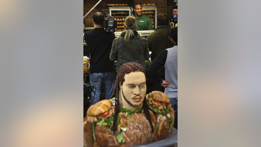 "Jarvis Jones, top center, the top 2013 NFL draft prospect from Georgia,  goes behind the counter after unveiling a food statue of himself, foreground, to announce his official Subway's Famous Fan title on Tuesday, April 23, 2013 in New York. Jarvis joins a roster of fellow ""Famous Fans"" that include Robert Griffin III, Justin Tuck, Michael Strahan, Ndamukong Suh, Blake Griffin and Michael Phelps.  More than 10 pounds of chicken were used to create the work of art, made by artist James Victor of Conshohocken, Pa.  (AP Photo/Bebeto Matthews)"